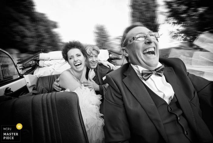 Arezzo Wedding Photographer   Image contains:black and white, bride, groom, tuxedo, car, leaving the ceremony