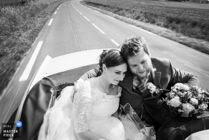 Île-de-France Wedding Photographer | Image contains: black and white, groom, bride, portrait, car, flowers, bouquet, highway