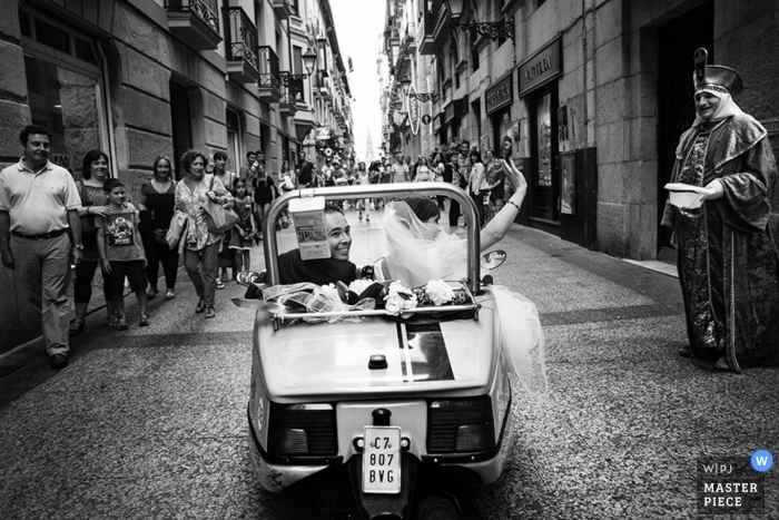 Madrid Wedding Photography   Image contains: vintage car, priest, cobblestone, bride and groom, black and white
