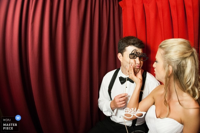 Omaha wedding photographer captured this playful photo of the bride and groom with props in the photobooth