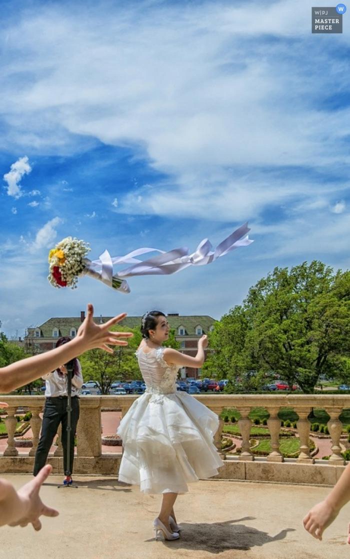 Tianjin-Hochzeitsfotograf schießt die Aktion der Braut, die den Blumenstrauß unter einem schönen blauen Himmel wirft