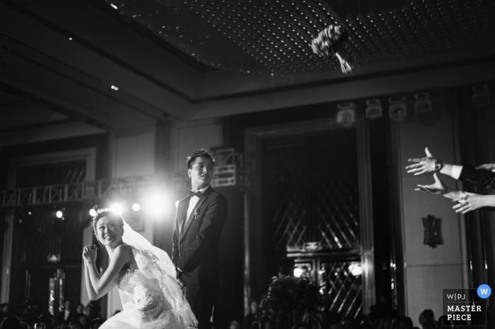 Dieses Schwarzweißfoto der Braut, die ihren Blumenstrauß an der Rezeption wirft, wurde von einem Shanxi-Hochzeitsfotografen aufgenommen