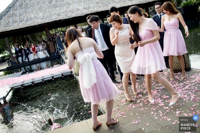 Bali Hochzeitsfotograf nahm dieses Foto von einem Hochzeitsstrauß fallen in einen Pool an der Rezeption