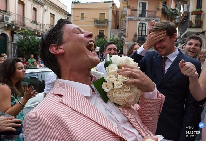 Der Hochzeitsfotograf von Catania hat dieses Foto eines Hochzeitsgastes aufgenommen, der lacht, als er den Blumenstrauß und das Gesicht des Bräutigams hinter sich fängt