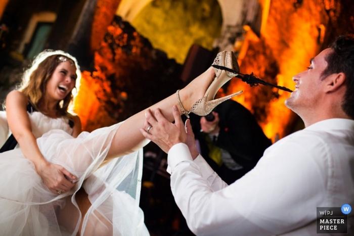 Der Hochzeitsfotograf aus Nordkalifornien friert die Aktion in diesem Bild ein, in dem der Bräutigam das Strumpfband mit den Zähnen beim Hochzeitsempfang entfernt