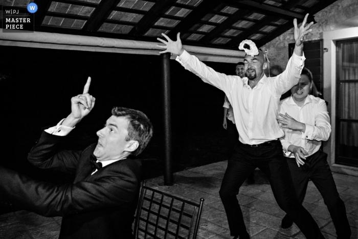 Der Hochzeitsfotograf aus Ljubljana hat die Aktion des Bräutigams beim Werfen des Strumpfbandes in diesem Schwarzweißfoto der Rezeption festgehalten
