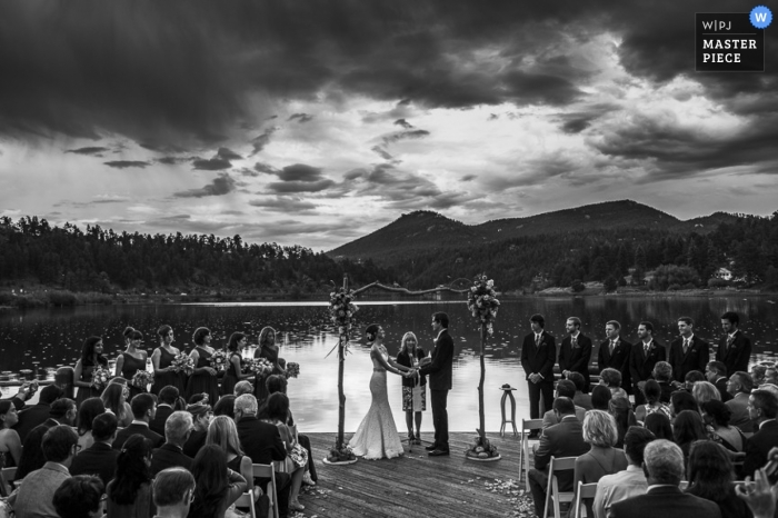 Vail wedding photographer created this black and white image of the wedding ceremony that is taking place on a lake with mountains in the background