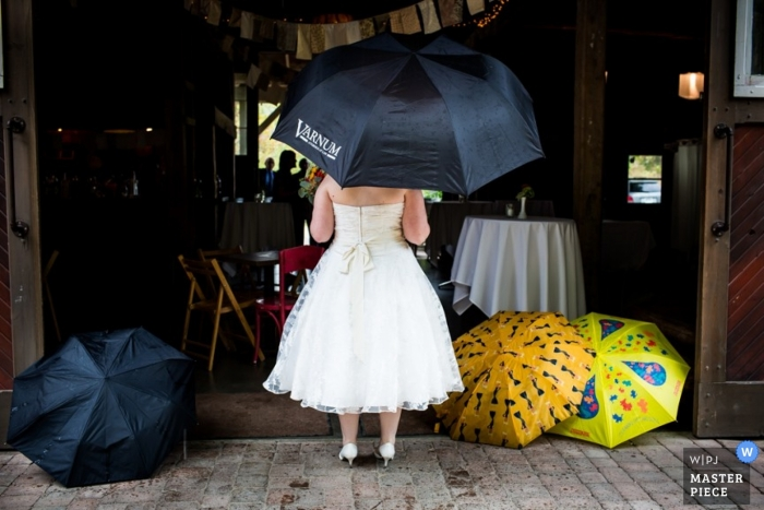 Chicago wedding photographer creates a picture of the bride standing at the doorway holding a black umbrella as she waits to go in