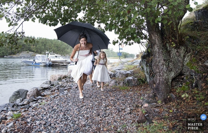The bride carries a large umbrella and runs alongside a river in this image composed by a Stockholm, Södermanland documentary wedding photographer.