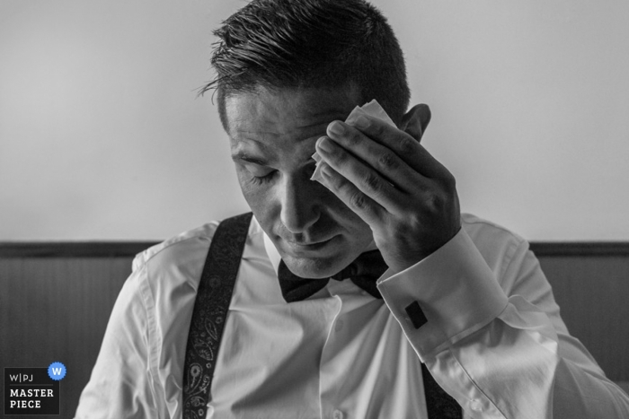 Madrid wedding photographer seized the moment in this black and white photo of the groom wiping his brow before the ceremony