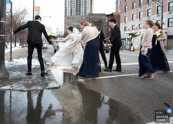 Chicago wedding photographer captured this photo of a bride getting assistance over a large puddle so she didn't ruin her dress