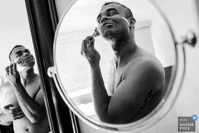 Charleston-Hochzeitsfotograf nutzte den Moment in diesem Schwarzweiss-Reflexionsfoto des Bräutigams, der sich vor der Hochzeit rasiert