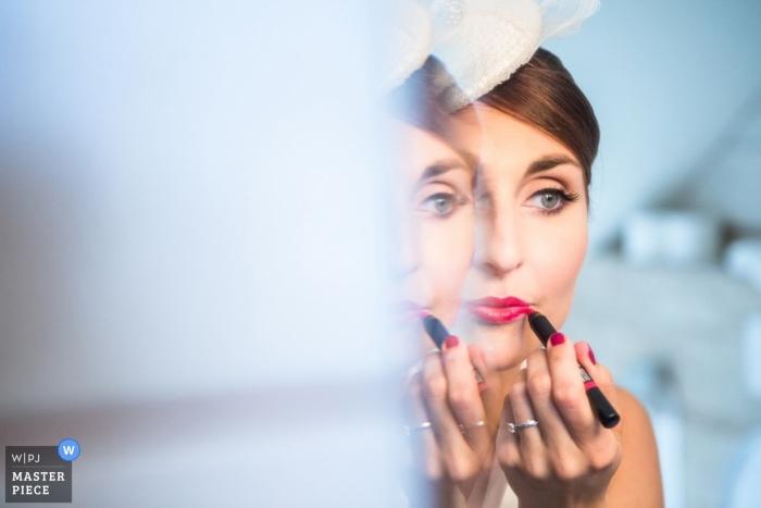 Der Prager Hochzeitsfotograf hat dieses Foto einer Braut aufgenommen, die vor der Hochzeit einen rosa Lippenstift auftrug