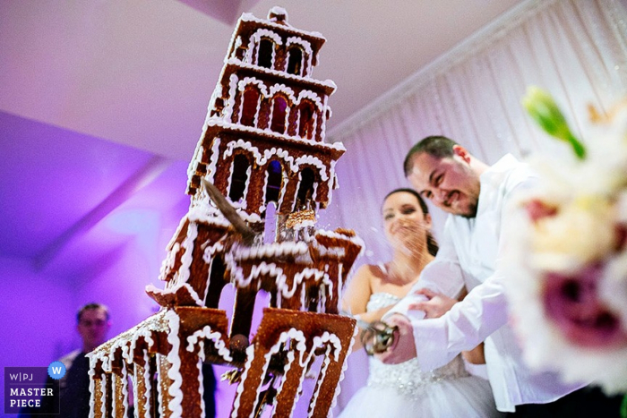 Croatia wedding photographer captured this photo of a groom using a sword to devastate a gingerbread tower