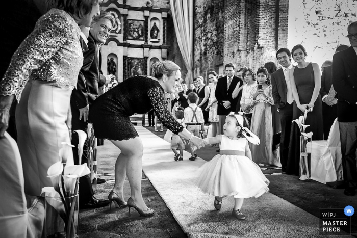 Playa del Carmen wedding photographer captured this black and white image of a rogue flower girl getting assistance in walking down the aisle
