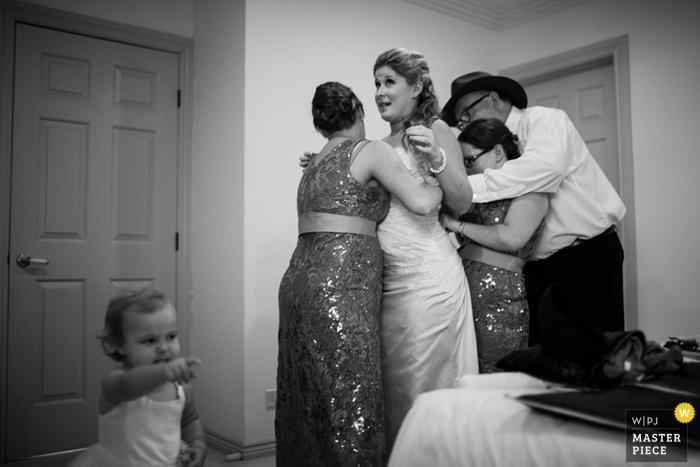 Photographe de mariage à Bali a capturé cette image de la mariée obtenir de l'aide sous tous les angles pour lacer sa robe de mariée