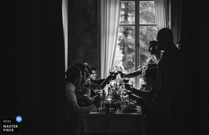 Przyjęcie weselne wznosi tosty na tym czarno-białym obrazie ślubnym stworzonym przez wielokrotnie nagradzanego fotografa ze Szwajcarii.