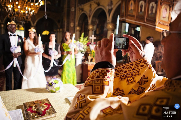 The priest takes a picture of the bride and groom in this award-winning wedding picture.