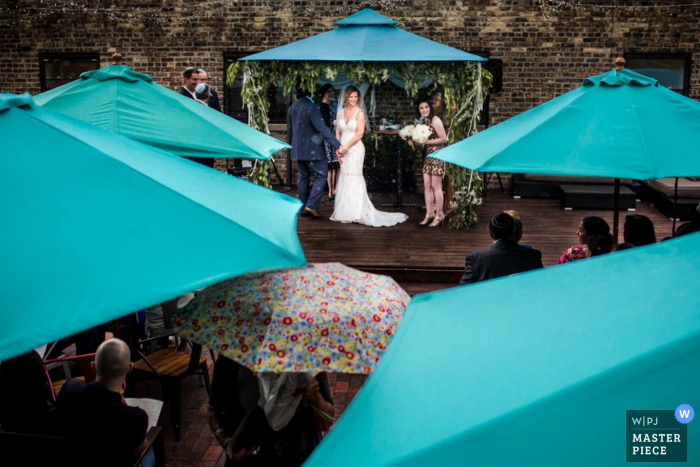 Guests stand under umbrellas as they watch the ceremony in this image created by a Chicago, IL documentary photographer.