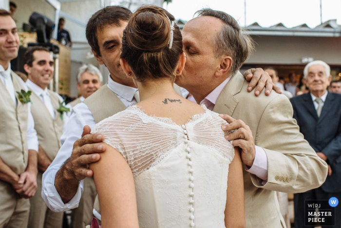 Rio de Janeiro wedding photographer captured this photo of the bride being kissed on the cheek by her father as the rest of the wedding guests watch nearby