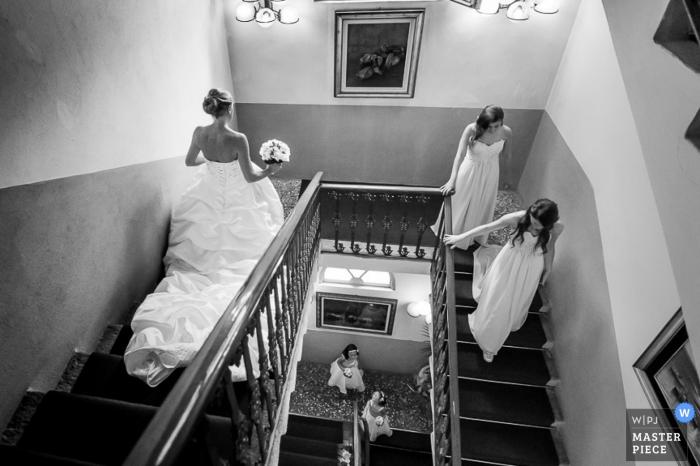 De bruid en de bruidsmeisjes lopen onderaan een trap in deze zwart-witte foto door een de huwelijksfotograaf van Lombardije.