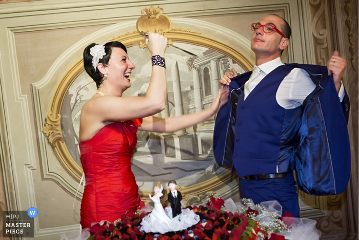 This photo captured by a wedding photographer shows the bride and groom humorously posing in front of their wedding cake