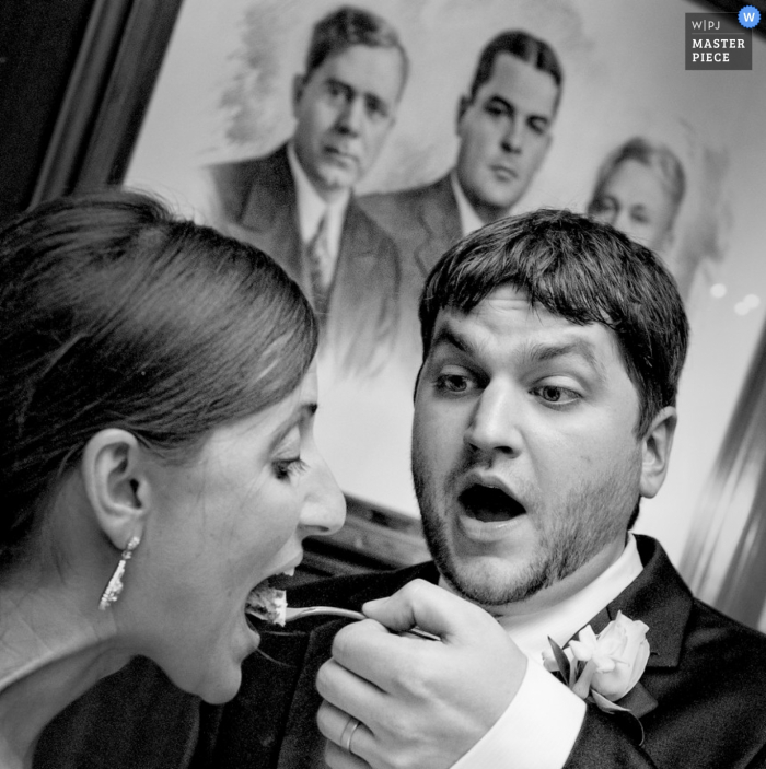 Baton Rouge wedding photographer captured this photo of the groom feeding the bride a bite of cake in front of a painting of men with disapproving looks