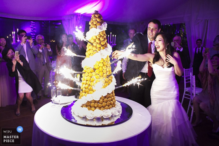Como wedding photographer captured this photo of the bride and groom lighting sparklers around their cake in a purple lit up room
