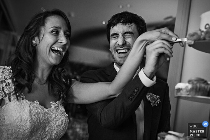 The bride and groom laugh as they cut their cake together in this black and white photo captured by a Hudson Valley, NY wedding photographer.