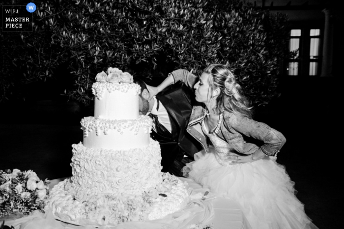 Trapani wedding photographer captured this black and white photo of the bride playfully pushing the grooms face into the wedding cake