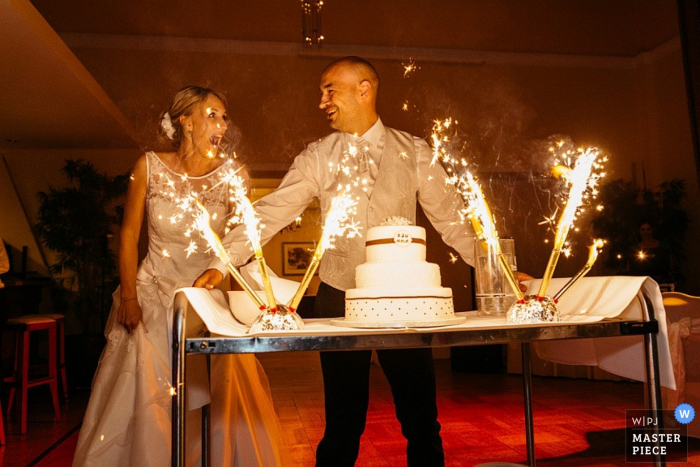 North Rhine-Westphalia	wedding photographer captured this photo of the bride and groom preparing to cut their cake as sparklers ignite on either side