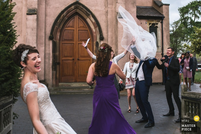 London bridal party laughing after the wedding ceremony as the brides veil flies through the air  - England wedding reportage photojournalism