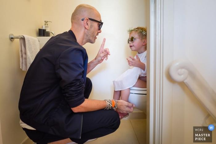 Amsterdamer Bräutigam spricht mit dem Blumenmädchen im Badezimmer - Noord Holland Hochzeitsfotojournalismus