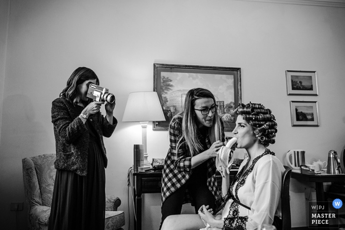 La novia de Roma come mientras se prepara el cabello antes de la boda: fotoperiodismo de bodas en Lazio