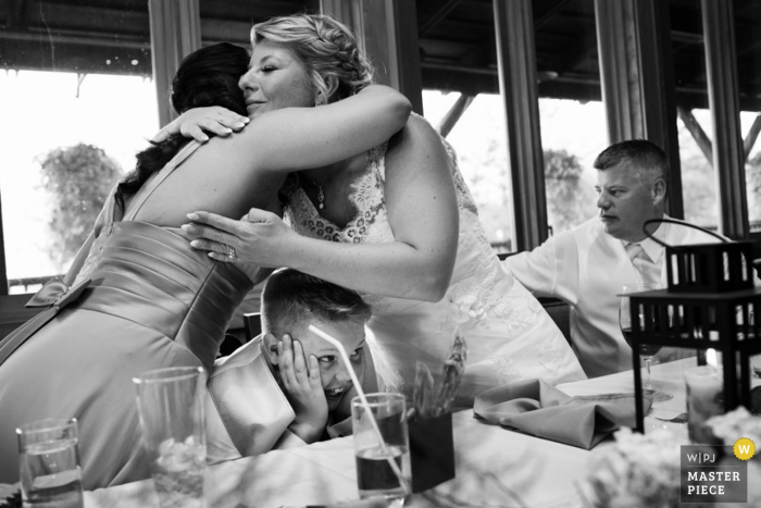 Victoria bride and maid of honor hug over little boy at the reception | British Columbia wedding photography