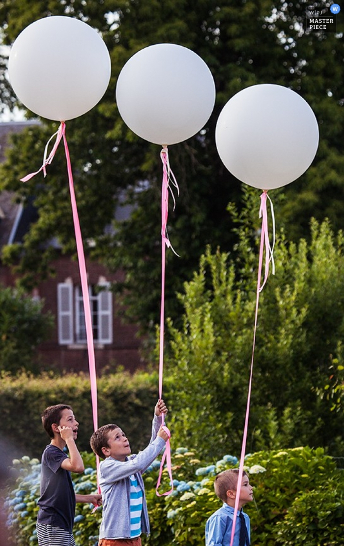 Paris kids hold balloons for the wedding | France wedding photojournalism