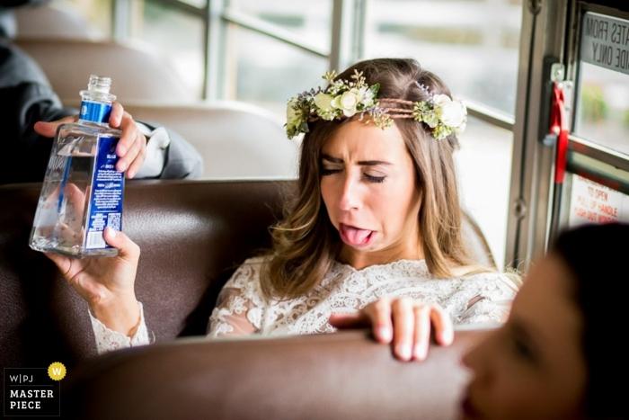 Fotografia di matrimonio della Pennsylvania del volto della sposa dopo aver preso un drink su un autobus | Momenti del giorno del matrimonio catturati a Philadelphia