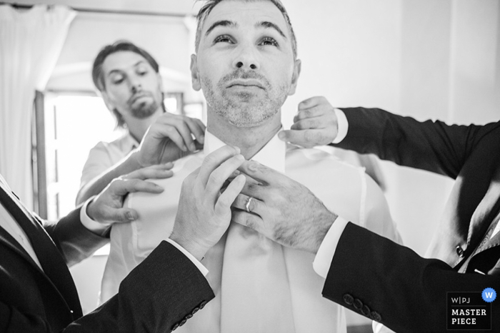 Venice groom getting some help with getting dressed for the wedding | Veneto wedding photography