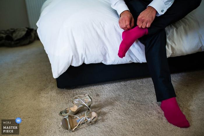 El novio de Devon se pone los calcetines mientras los tacones yacen a su lado   Foto de boda de inglaterra
