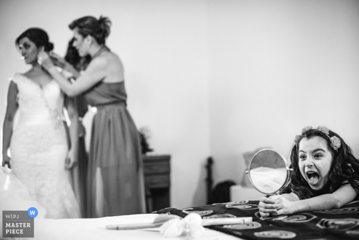 La niña se mira en el espejo mientras la novia se prepara para la boda
