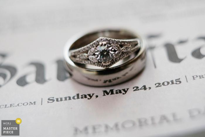 San Jose wedding photography detail of rings on newspaper