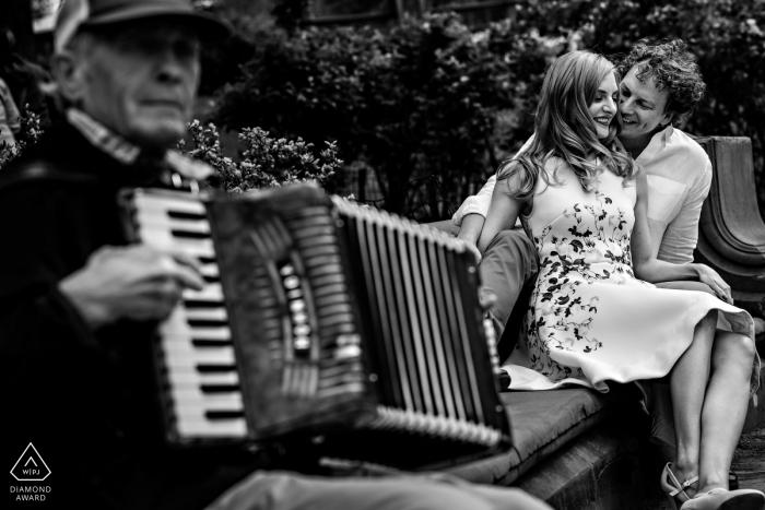 Schwarzweiss-Verlobungsporträt von den Paaren, die mit einem Mann spielen das Akkordeon sitzen   Winnipeg Hochzeitsfotograf