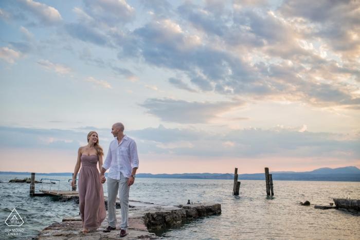 Photographie d'engagement de Padoue. Séance photo avant le mariage sur la jetée en pierre menant au quai au bord de l'eau.
