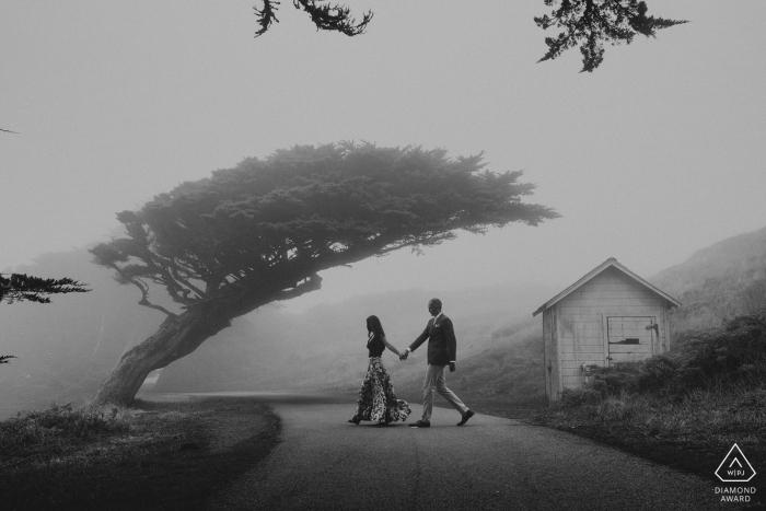 Photo de fiançailles en Californie. Ils traversent la route main dans la main dans ce portrait noir et blanc brumeux.