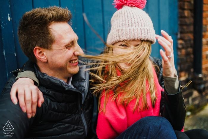 England Verlobungsfotograf. Winterpaarporträts mit Jacken und Mützen im kalten Wind.