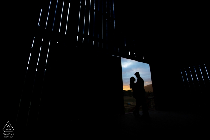 Une vieille grange rustique en Colombie-Britannique est utilisée pour encadrer ce couple de fiancés lors de leur séance de portrait