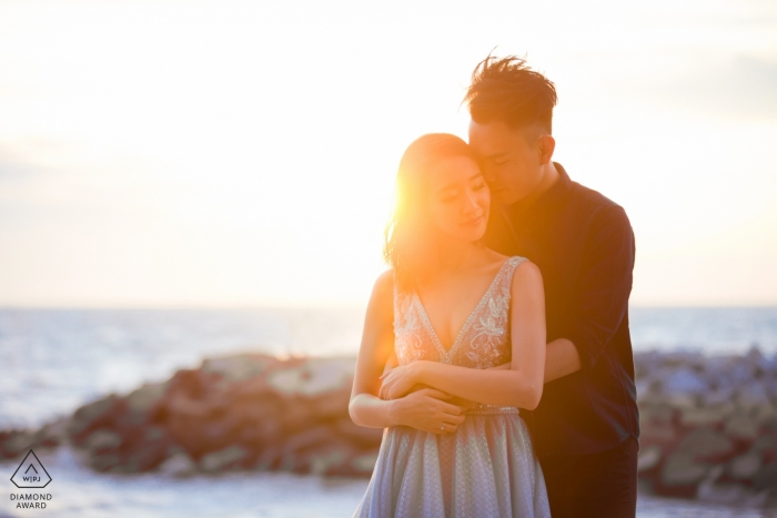 Malaysia couple embraces at the jetty by the ocean for their pre-wedding Photos
