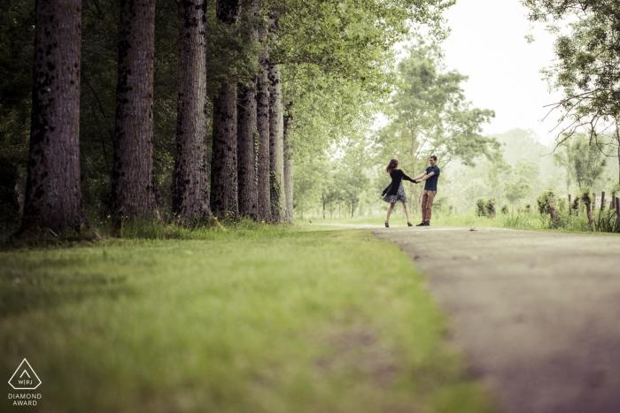 Portraits de fiançailles Pays de la Loire | couple nouvellement fiancé fait une promenade ludique sur le sentier à côté de la forêt avec de grands arbres