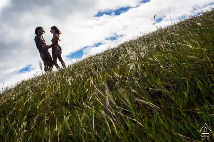 Madrid pre-wedding portraits of a couple in a grassy field | tilted horizon with a blue sky and clouds