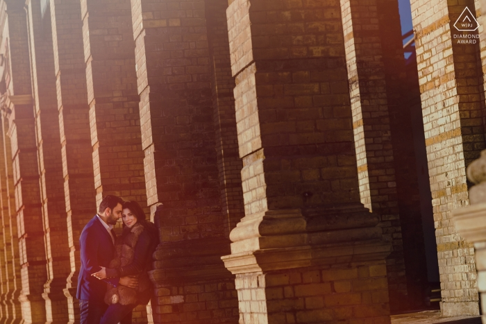 Brick pillars in London add to the starkness of this outdoor engagement portrait